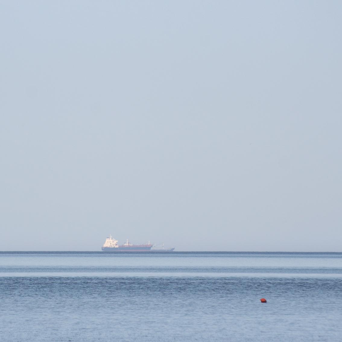 Kamēr mēs ēdām, tālumā kuģītis un viena sarkana boja kā signālpunkts. Nē, kā milzu dzērvene.