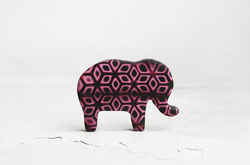 Mokume gane tehnikā darināts zilonis, kuram izmantota tieši tā pati kubu konstrukcijas tekstūrplāksne, taču mainītas sagataves materiāla nianses un raksta novietojuma virziens. Piespraužams. 13 delfīni.