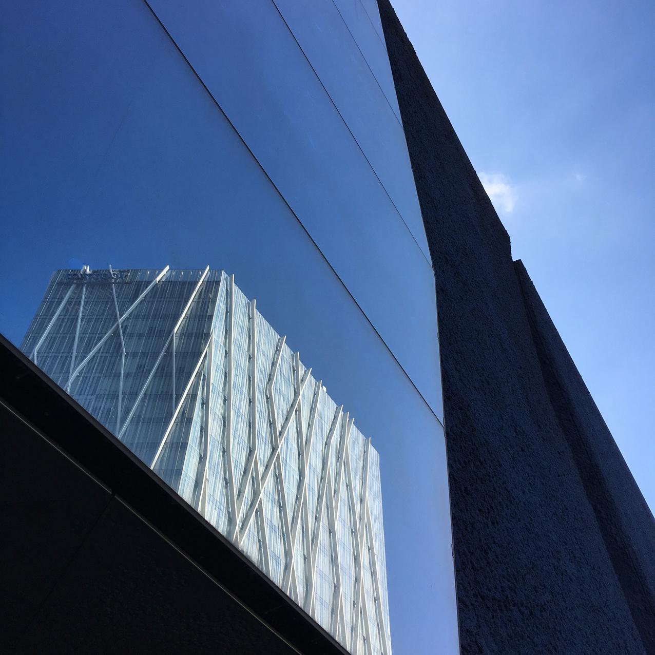 Stikloti ielaidumi, kuros tiem augstajiem namiem spoguļoties.